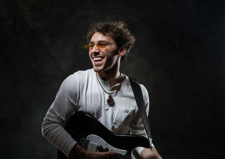 Curly and smiling caucasian male musician standing in a dark studio on a grey background, wearing casual white shirt and glasses while playing an electric guitar. 版權商用圖片