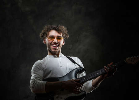Curly and laughing male musician standing in a dark studio on a grey background, wearing casual white shirt and glasses while playing an electric guitar.