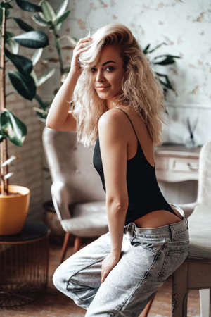Well-shaped and sexy young woman with blonde curly hair sitting on a wooden table in a bright room with plants, wearing body costume and unzipped jeans, showing her curves. Looking seductive and slightly smiling.