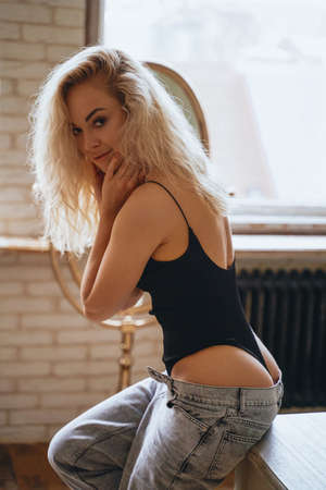 Well-shaped and sexy young woman with blonde curly hair sitting on a wooden table in a bright room in front of plants, wearing body costume and unzipped jeans, showing her curves. Looking seductive and slightly smiling.