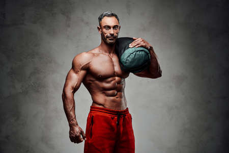 Masculine sportsman isolated on the grey background wearing sport shorts with naked torso, holding a weight bag on his shoulder looking strong Stock Photo
