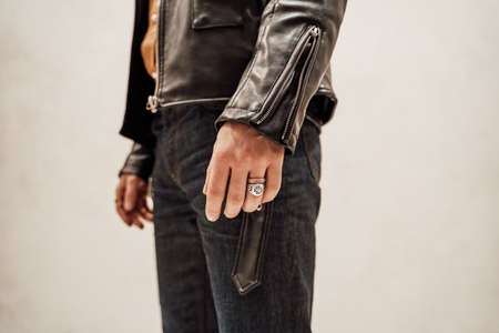 Close-up photo of the male hand with two rings and leather coat