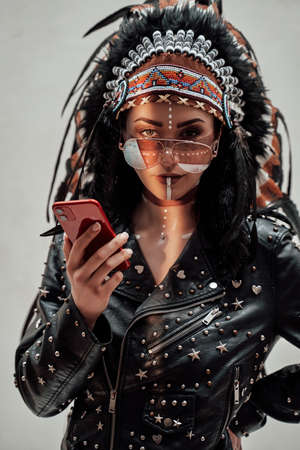 Confident young woman posing in a studio wearing tribal headdress, leather jacket and sunglasses, while looking on her smartphone