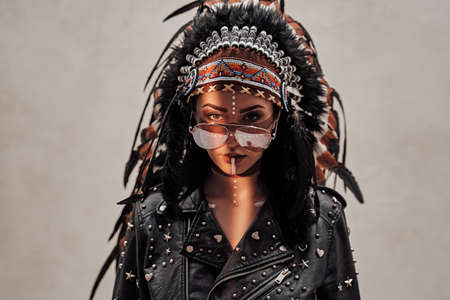 Attractive woman posing in sunlight wearing indian feather headwear, leather jacket and sunglasses, looking smooth