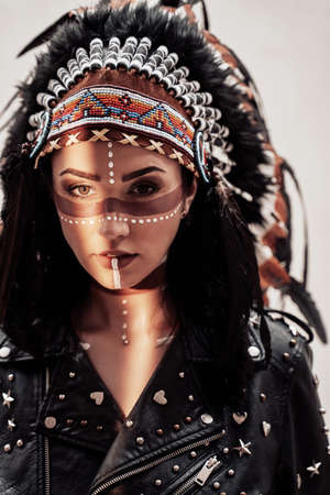 Beautiful and confident female wearing American indian traditional headdress, leather jacket and sunglasses while posing in a bright studio and looking serious