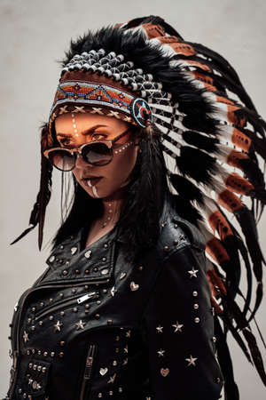 Assertive and cool young woman posing on a white background, wearing native american headdress, leather coat and sunglasses, looking dangerous with tribal make-up on