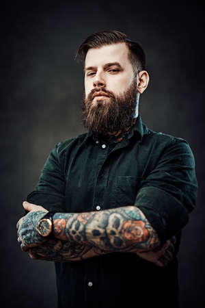 Cool bearded guy with tattooed neck and hands posing in dark studio