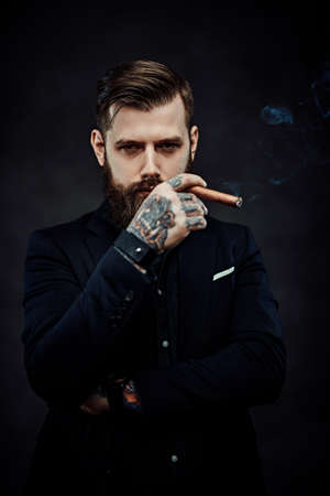 Elegantly dressed bearded male with tattoos on his neck and hand lights a cigar. Brutal young businessman smokes a cigar in a dark studio.