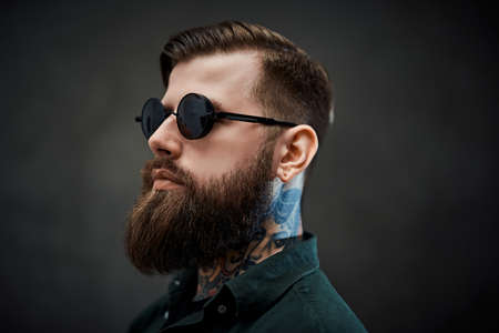 Closeup portrait of a cool bearded male in sunglasses on a dark background