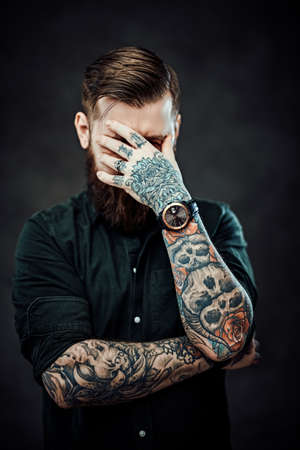 Cool bearded tattooed man posing on camera covering his face with his hand in a dark studio