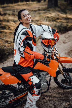 Happy brunette girl wearing motorcycle outfit sitting on her bike off-road in the woods