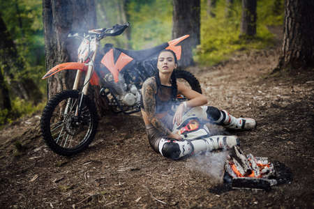 Young tattoed racer girl warming up while sitting next to the bonfire in the woods Фото со стока