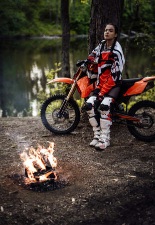 Charming young female racer wearing motocross outfit on her bike and warming up next to a bonfire in the woods Фото со стока