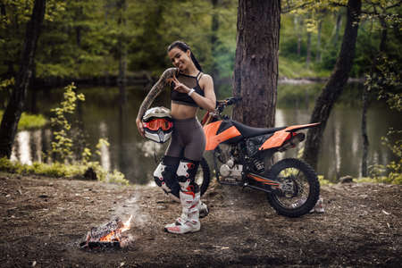 Cheeky racer girl wearing motocross outfit holding helmet and posing on a camera next to the bonfire in the woods