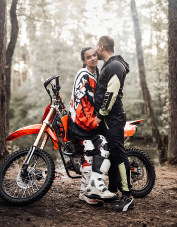 Attractive couple hug standing next to a motocross bike and bonfire in the woods