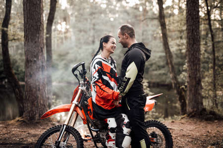 Happy couple hold hands standing next to a motorcycle in the woods