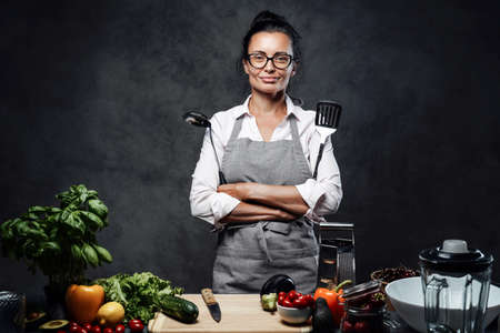 Beautiful middle-aged female chef posing next to a table with fresh vegetables in kitchen. Healthy and proper nutrition on a diet. Studio photo on a dark background