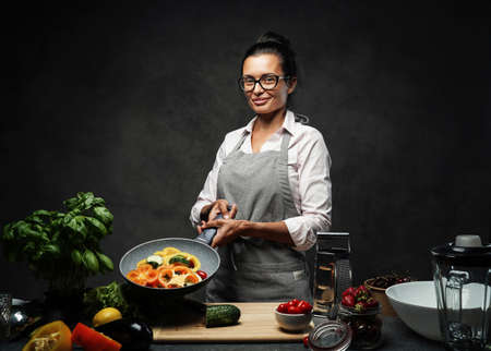Happy mature woman cooking in kitchen, holds a pan with chopped vegetables and looking on the camera. Healthy and proper nutrition on a diet. Studio photo on a dark background