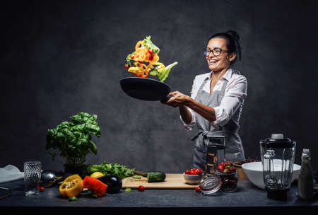 Happy middle-aged female chef tossing chopped vegetables in the air from a frying pan. Healthy food concept. Studio photo on a dark background Archivio Fotografico