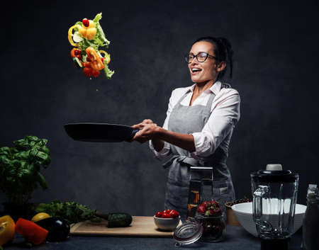 Beautiful mature woman cooking vegetable salad in the kitchen, tosses vegetables from the pan. Healthy food concept. Studio photo on a dark background