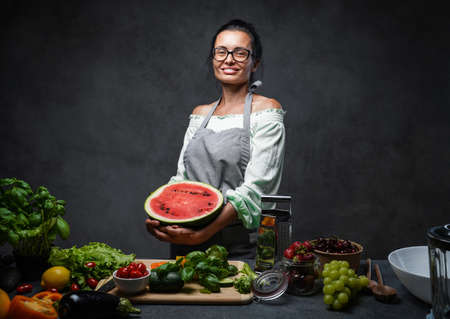 Middle-aged female chef holds half the watermelon in kitchen, smiling and looking on the camera. Healthy and proper nutrition on a diet. Studio photo on a dark background 스톡 콘텐츠