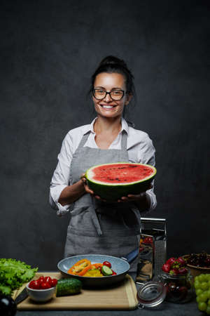 Beautiful mature female chef holds half the watermelon in kitchen, smiling and looking on the camera. Healthy and proper nutrition on a diet. Studio photo on a dark background