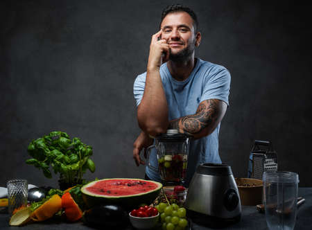 Handsome tattooed male in blue shirt leaning on a blender in kitchen. Homemade healthy fruit smoothie. Studio photo on a dark background 스톡 콘텐츠