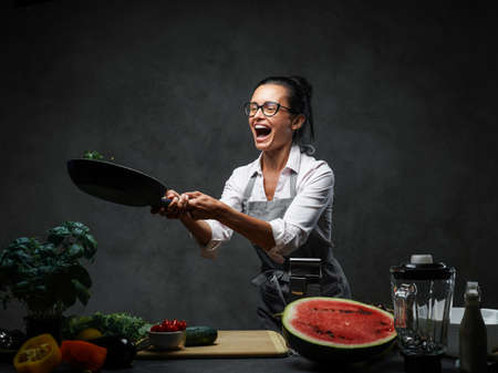 Emotional mature female chef tossing chopped vegetables from a pan. Healthy food concept. Studio photo on a dark background