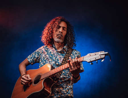 Middle aged hispanic man musician in a hawaiian shirt playing guitar on a dark illuminated by blue and red light. Concept of music, hobby, festival Stockfoto