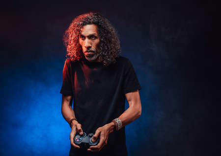 Middle aged hispanic male with long curly hair playing video game with joystick, looks focused. Hi-tech concept with vr glasses