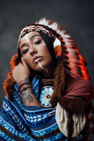 Studio portrait of a beautiful American Indian girl with tattoo on hand in colorful traditional ethnic costume on a dark background Archivio Fotografico