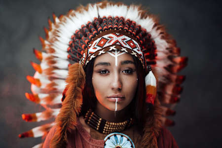 Close up portrait of a attractive young American Indian woman with make up in traditional feather hat and clothes on a dark background