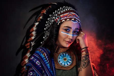 Portrait of a beautiful American Indian woman in ethnic costume and traditional make up on dark background with smoke illuminated by red light Archivio Fotografico