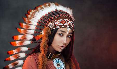 Portrait of a beautiful American Indian woman in ethnical costume and traditional make up. Studio portrait on a dark background Stock fotó