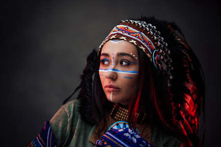 Portrait of a beautiful American Indian woman in ethnical costume and traditional make up. Studio portrait on a dark background
