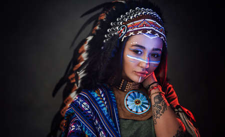 Charming American Indian girl with tattoo on hand in traditional make up hat and clothes on a dark background illuminated by red and blue light