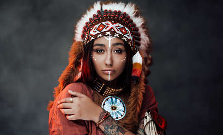 Studio portrait of a beautiful American Indian girl with tattoo on hand in colorful traditional ethnic costume on a dark background