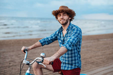 Young man is riding his bicycle on the seacoast, smiling