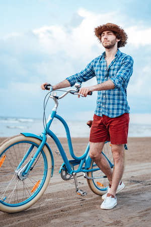 Cool boy with a straw hat on his head is walking on the beach with his blue bike
