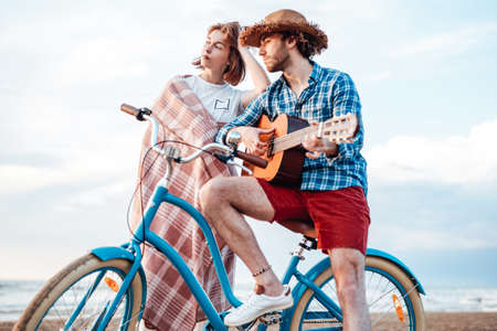 Couple with their bicycles. Boy is playing on the guitar. Girl is wrapped in pink blanket, looking at the sunset