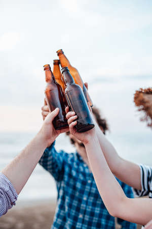 A group of friends, drinking beer on the beach, chilling