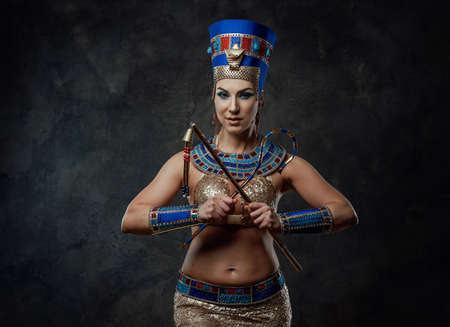 Young woman in egyptian costume posing in the studio with dark walls