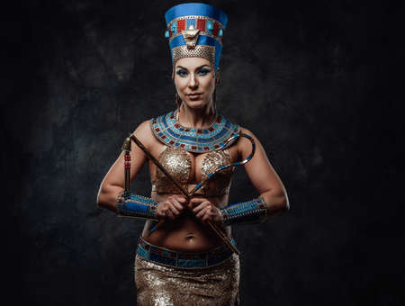 Beautiful woman in egyptian costume with the signs of power