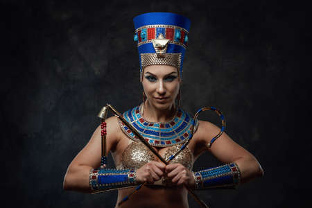 Sexy woman in traditional blue and gold egyptian costume, posing in the studio with the black walls Stock fotó