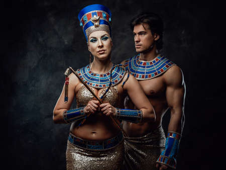 Woman and man in blue and gold egyptian costumes, posing in the studio with black walls Stock fotó