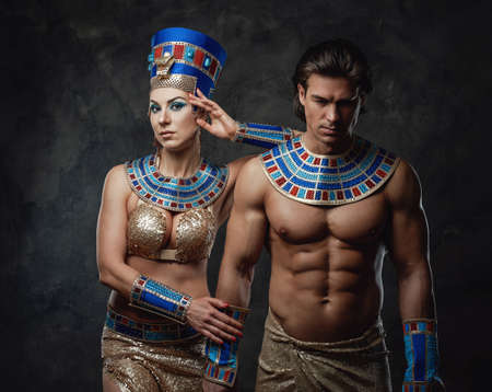 Sexy woman and man in egyptian costumes posing in the studio with the dark walls.