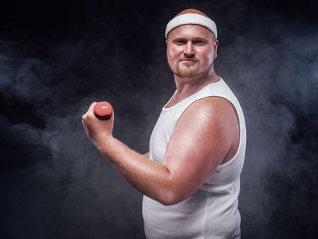 A plump man works out with a small dumbbell. He is wearing a white tracksuit and looks very pleased.