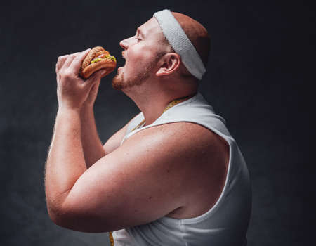 Chubby man biting a very big hamburger, holding it with two hands, standing in a sport costume and having a white bandage on his head