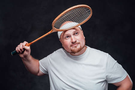 A fat and bald man with red cheeks in a tracksuit holds a racket over his head and smiles tiredly