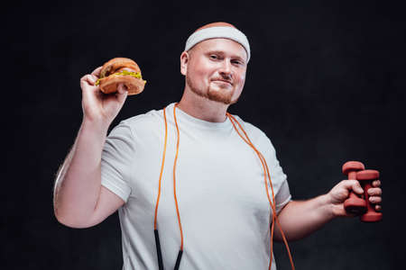 Fat men with a white headband on his bold head is holding a hamburger in one hand and two red dumbbells in other one, having an orange skipping rope on his neck, smiling at the camera
